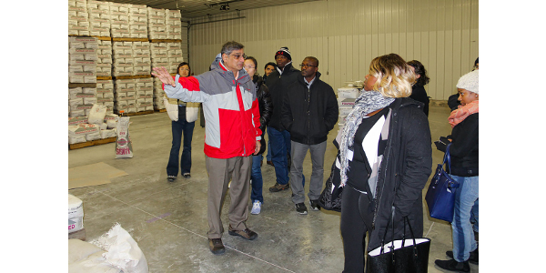 "Course coordinator Bhadriraju ""Subi"" Subramanyam explains evaluations of pest control measures that are implemented in an operation while touring the seed warehouse at the KSU Agronomy Farm. (Courtesy of IGP Institute)"