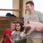 WIU junior Will Taylor shows a baby pig to Macomb second graders Blaze Childs and Carynna Elmore. (Courtesy of WIU)