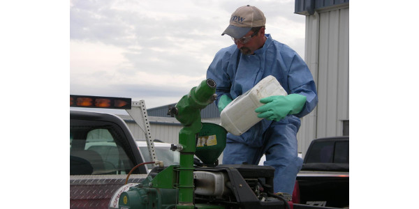 Personal protective equipment should always include gloves, long pants, long-sleeved shirt, shoes, and socks. Some situations also call for protective eye wear and coveralls. (Courtesy of the Pesticide Safety Education Program)