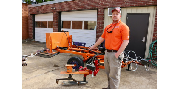 Clemson University graduate student Jordan Breland shows the cultivator he is building to escalate soil around peach trees. (Image Credit: Scott Miller)