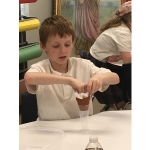 Ian Parks, a student of Ms. Mooney's fourth grade class at St. Mary's School in Taylorville conducts an experiment on water filtration during at a recent Ag in the Classroom program. (Courtesy of University of Illinois Extension)