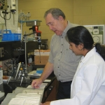 Ted Hymowitz and Leina Mary Joseph look through a binder of 11,000 tested soybean samples.