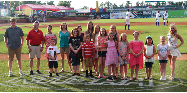 Statewide winners in the Kentucky Department of Agriculture's Poster and Essay Contest were recognized with Agriculture Commissioner Ryan Quarles, second from left, and Miss Kentucky Laura Jones, right, between innings of the Lexington Legends game on Friday at Whitaker Bank Ballpark. (Kentucky Department of Agriculture photo)