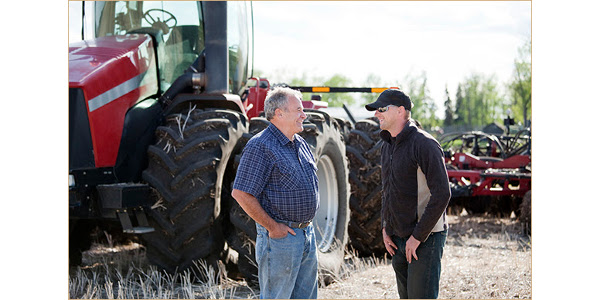 Two men with tractors on the farm. It is seeding time in the spring.
