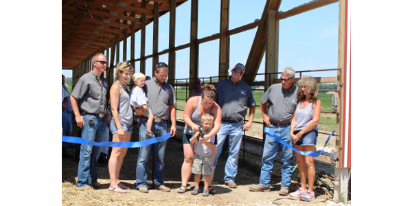 The Gronewold family celebrates the opening of their new cow-calf deep-pack monoslope barn at their recent Open House attended by more than 300 people. Pictured left to right – Jason Wildrick, Maddie Gronewold, Rawson Gronewold, Ashton Gronewold, Brooke Davidson (helping Haxton Gronewold cut the ribbon), Evan Davidson, Merlin Gronewold and Jolene Gronewold. (Courtesy of IL Livestock Development Group)