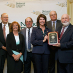 Representative Cheri Bustos of Illinois accepts NFU's Golden Triangle Award. Pictured from left to right are: Rick Duvall, Christy and Jerry Lowery, Rep. Cheri Bustos, Wendel Lutz and Norbert Brauer. (Courtesy of Illinois Farmers Union)