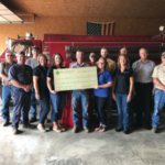 FCS Financial Rural Community and Agriculture Foundation presents $5,582 to the Novelty Plevna Rural Fire Department to purchase a rescue bin harness set. Left to right: Dan Devlin, FCS Financial Director; Byron Harder, Fire Department Volunteer; Randy Doss, Fire Department Volunteer; Jacob Bryant, Fire Department Volunteer; Connie Kuhman, FCS Financial; Kathryn Whisenand, FCS Financial; Kent Franke, Fire Department Volunteer; Stanley Bowen, Fire Department Volunteer; Sadie Barnes, FCS Financial; Ben Bradley, Fire Department Volunteer; Debbie Ragsdale, FCS Financial; Jason Doss, Fire Department Volunteer; Dave Janish, FCS Financial CEO; and Randall Smoot, Fire Department Volunteer. (Courtesy of FCS Financial)