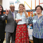 Celebrating Wolfpack-style at the NIFA awards ceremony were (left to right): Rebecca Goulter, NoroCORE assistant director; Sonny Ramaswamy, NIFA director; Lee-Ann Jaykus, NoroCORE director; and Elizabeth Bradshaw, NoroCORE communications director. (Courtesy of NC State University)