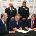 Agriculture Commissioner Ryan Quarles, seated at right, and Michael O'Gorman, center, executive director of the Farmer Veteran Coalition, sign a Memorandum of Understanding continuing the partnership of the FVC and the Kentucky Department of Agriculture as FVC President Gary Matteson, seated at left; Ray Harris of the Kentucky Department of Veterans Affairs, standing at left; and Col. Shon Adams of the Kentucky National Guard look on. (Kentucky Department of Agriculture photo)