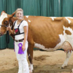 Miriah Dershem of St. Johns, Michigan, stands with her cow Rubie after winning grand champion of the Red and White show during Michigan 4-H Youth Dairy Days in 2016. (Photo by Christie Dershem)