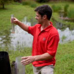 At a stormwater runoff site in Morrisville, Gregg checks water samples. (Courtesy of NC State University)