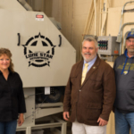 Brenda Bakken, CEO, Lone Star Enterprises, left, stands near the Triple Lone Star roller mill that the company recently donated to SDSU. Bakken is joined by Dr. Joseph Cassady, SDSU Animal Science Department Head, and John Goebel, SDSU feed processing facility manager. (Courtesy of SDSU)