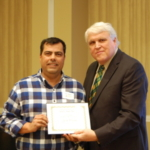 Juan Osorno, left, receives the Larson/Yaggie Excellence in Research Award from David Buchanan, associate dean for academic programs. (NDSU photo)
