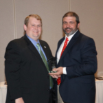 Ryan Bivens of LaRue County, right, accepts the KSA Distinguished Service award from KSA Vice-President Fred L. Sipes of Meade County. (Courtesy of Kentucky Soybean Board)