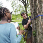 Amelia Baylon, NRES student, helps middle-school students measure a tree during 2017 Expanding Your Horizons STEM workshop. (PHOTO: Carol Lea Spence)