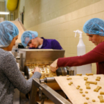 Participants in the IGP–KSU Pet Food Formulation for Commercial Production course place pet treats on a conveyor belt in a baking lab at AIB International in Manhattan, Kansas.(Courtesy of IGP–KSU)