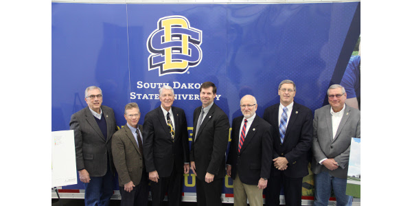 First Bank and Trust is making a $500,000 investment in the new SDSU Precision Agriculture facility. SDSU President Barry H. Dunn (left), and College of Agriculture and Biological Sciences Interim Dean Don Marshall joined Van. Fishback, Chairman, Fishback Financial Corporation, and Kevin Tetzlaff, President of First Bank & Trust (center) to accept the gift along with SDSU Agriculture and Biosystems Engineering Department Head Van Kelley, South Dakota Agricultural Experiment Station Interim Director Bill Gibbons, and SDSU Agronomy, Horticulture and Plant Science Department Head David Wright. (Courtesy of SDSU)