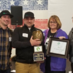 MI Local's Alex Wiesen (left) and Jason Warren (tightly gripping trophy) receive the 2017 Chinook Cup from the Hop Growers of Michigan. (Courtesy of MSU Extension)