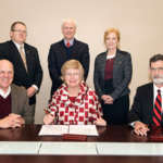 Signing a cooperative agreement Feb. 7 for the NCTA-MSU Poultry Program based at Curtis, Nebraska are, seated, left-right, George Hopper, dean of MSU's College of Agriculture and Life Sciences; Judy Bonner, MSU provost and executive vice president; and Ron Rosati, dean of the Nebraska College of Technical Agriculture; back row, left-right are Doug Smith, NCTA chair of Animal Science and Agricultural Education; Peter Ryan, MSU associate provost for academic affairs; and Professor Mary Beck, head of MSU's Department of Poultry Science. (Photo by Beth Wynn/MSU)