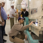 Jason Watt, Buhler milling instructor at the IGP Institute, shows the wheat product to participants in the Buhler–KSU Expert Milling course during a wheat conditioning exercise at the Hal Ross Flour Mill. (Courtesy of KSU-IGP Institute)