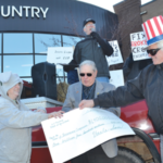 """""""Uncle Sam"""" hands over billions of dollars in public funds to """"Big Insurance"""" during a Land Stewardship Project press conference in front of NAU Country Insurance's headquarters in Ramsey on March 12. NAU is one of 15 insurance companies designated by the federal government to sell crop insurance. (Courtesy of Land Stewardship Project)"""
