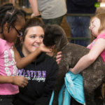WIU agriculture student Raelynn Thompson introduces two second graders to some of the animals at the WIU livestock center. (Courtesy of WIU)