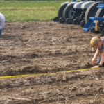 Joe Luck (left) and Rachel Stevens check seed placement of a multi-hybrid planter being tested as part of a collaborative research project being conducted by university researchers, industry and growers. (Courtesy of University of Nebraska-Lincoln)