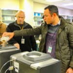 Participants in the IGP–KSU Grain Purchasing course pour wheat samples in a moisture meter at the USDA Federal Grain Inspection Service office in Kansas City, Missouri. (Courtesy of KSU-IGP Institute)