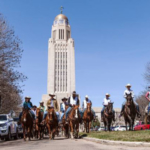 Governor Pete Ricketts (left-center) rides down Goodhue Boulevard with members of the UNL Rodeo Team in front of the Nebraska State Capitol to celebrate Rodeo Week. (Courtesy of Office of Governor Pete Ricketts)