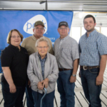 After cutting the ribbon to signify the opening of Austin Betzold's new pig barn, the family poses for a picture. Austin Betzold (right) thanked his family in a welcoming speech for their guidance and support of his new livestock venture. Pictured from left is Austin's aunt, Barb Paine; grandma, Dorothy Betzold; uncle, Mark Paine; and father, Bruce Betzold. (Courtesy of IPPA)