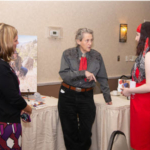 Temple Grandin chatting with Meredith Cox, right,and her mother, Amber Cox, at the Zonta Club luncheon, May 5, 2018. (Courtesy of CSU)