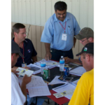 Kapil Arora, extension agricultural engineer (center) works with students during the drainage design exercise at the Iowa Drainage School. (Courtesy of ISU Extension and Outreach)
