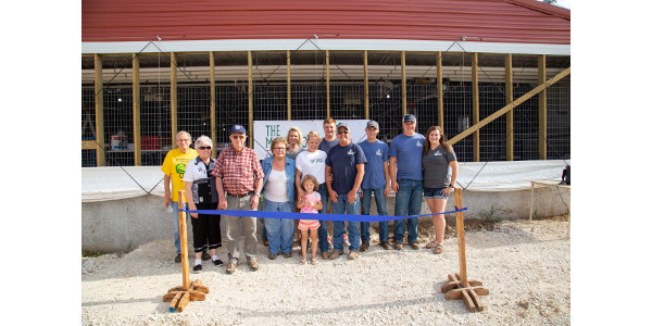 Doug Harter, and family, prepare to cut the ribbon at the open house for their new big barn outside of Barry, IL. The Harters have been raising pigs and farming for five generations. (Courtesy of Illinois Pork Producers Association)
