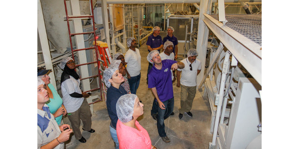 Justin Howie, plant manager, for Farmer Direct Foods, explains to participants the machinery in the flour mill while they toured. (Courtesy of KSU-IGP Institute)