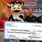 Representatives from DFA, UDIM and SpartanNash along with Detroit Red Wings player Justin Abdelkader presented a check for more than $26,000 to the Food Bank Council of Michigan. The money will be used to purchase fresh milk for food insecure families. (Courtesy of DFA)