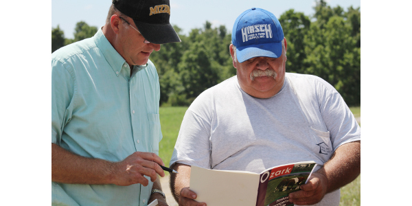 MU Extension agronomy specialist Tim Schnakenberg, left, and Ozark County farmer J.D. McKee look at available warm-season native grass varieties. (Photo by Linda Geist)