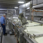 Klondike's largest seller is feta, made in the automated production line. On left, milk pumped into the far vat cells will shuttle along until it is cut into chunks and drained off in the forms shown at right. (Photo: David Tenenbaum)