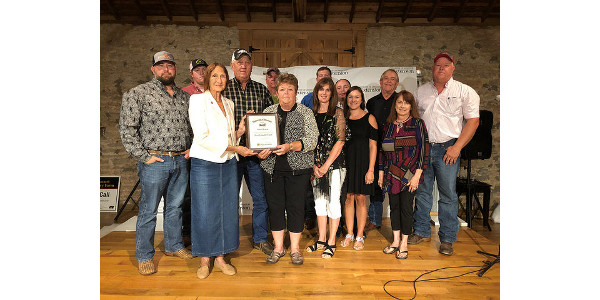 "Jackie Warfel, volunteer with Greene County MU Extension, presents the first ""Jackie Warfel Most Valuable Farm Award"" to the Hawk family of Walnut Grove. Their farm has been in the family and in continuous operation since 1833. (Courtesy of University of Missouri Extension)"
