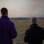 Two Kansas State University pilots fly an unmanned aircraft over a tallgrass prairie prescribed burn to gather smoke emissions data. The pilots are part of a large collaborative project that is using unmanned aircraft to improve the Kansas Flint Hills Smoke Management Plan and determine smoke constituents. (Photo credit: David Burchfield, Kansas State University)