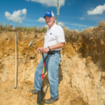 UK soil scientist Lloyd Murdock shows the fragipan layer in the soil in a pit at the UK Research and Education Center farm in Princeton. (Photo by Stephen Patton, UK agricultural communications)