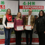 From left, Jennifer Hulme, Kelsey Spotts and Nate Weber receive the Achievement in Service award from Interim Program Leader Andrea Nelson. (Courtesy of ISU Extension and Outreach)