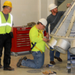 Participants perform maintenance on a distributor under the guidance of instructor Jeff Schwab. (Courtesy of IGP Institute, Kansas State University)
