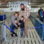 The Defenbaugh family cuts a ribbon to signify the opening of their new 2,496 head wean-to-finish pig barn outside of Blackstone, Ill. (Courtesy of Illinois Pork Producers Association)