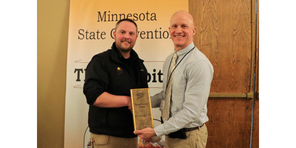 Tanner Bruse, Ag & Conservation Programs Manager (MN) for Pheasants Forever and Quail Forever, presents the Brood Booster Award to Brad Redlin, manager of the Minnesota Agricultural Water Quality Certification Program. (Courtesy of Minnesota Department of Agriculture)