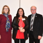 Sharon Toth, UDIM CEO, (left) and Jim Reid, Michigan dairy farmer and UDIM President, (right) present the 2019 Excellence in Dairy Promotion award to Ramona Ann Okkema-Clark of Blanchard, Michigan. (Courtesy of United Dairy Industry of Michigan)