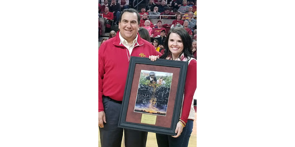 Dan Robison, endowed dean of the College of Agriculture and Life Sciences, presents Elizabeth Burns-Thomopson with the 2019 Emerging Iowa Leader Award from the Iowa State University College of Agriculture and Life Sciences at center court of Hilton Coliseum. Burns-Thompson is regulatory affairs counsel for the Iowa Corn Growers Association. (Courtesy of Iowa State University College of Agriculture and Life Sciences)