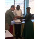 Peter Goldsmith, Soybean Innovation Lab principal investigator and director, presents a certificate of completion to a Ghana School Feeding Program caterer upon her completion of a Soy in School Lunch training led by Chef Nutepe Karte y-Attipoe, an Accra-based Ghanaian chef. (Courtesy of University of Illinois)