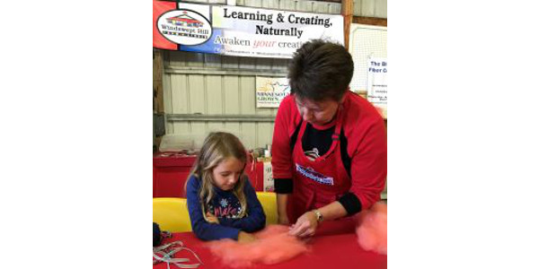 Wendy Wustenberg helps a young visitor make a pink wool angel. (Photo courtesy of Wendy Wustenberg)