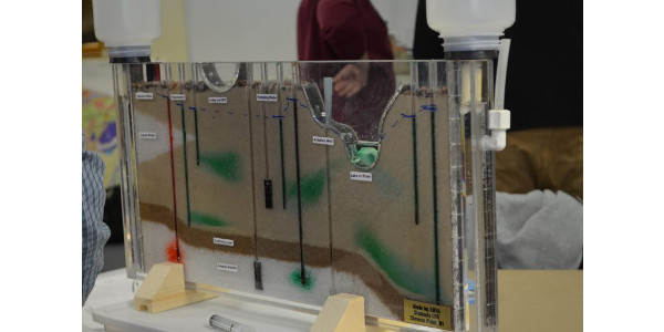 """""""One of the best tools we have [for learning about groundwater] is what we call the Sand Tank Groundwater Model. It's a small plexiglass container that represents a cross section of the earth's crust. We can add water to it, we can add dye to it which helps visualize how that groundwater moves through the landscape to maybe a lake, river or stream and can illustrate how things we do at the landscape can impact the quality below,"""" said Masarik. (Courtesy of UW-Extension)"""