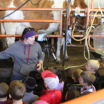Former NAYC member and current UNL Extension employee Melisa Konecky discusses how cows are milked at her family dairy operation. (Courtesy of Nebraska Department of Agriculture)